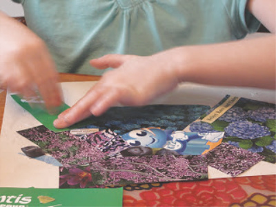 child gluing clippings on construction paper