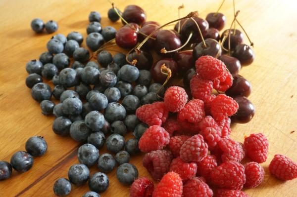blueberries, raspberries and cherries on cutting board