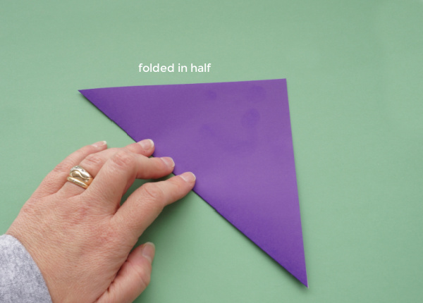 origami paper folded in half for paper snowflake