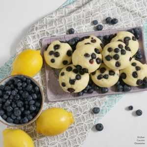 lemon blueberry pancake muffins on tray with blueberries and lemons
