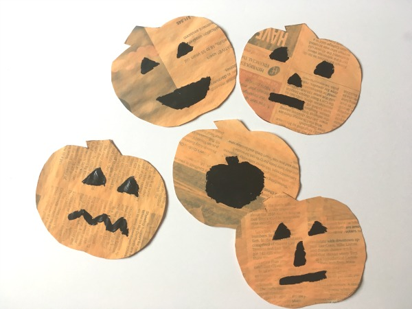 newspaper pumpkins with faces painted on