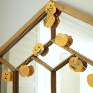newspaper pumpkin garland hanging on mirror