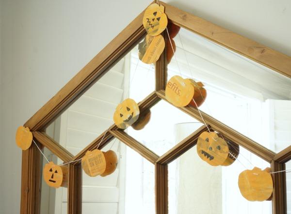 newspaper pumpkin garland hanging on mirror