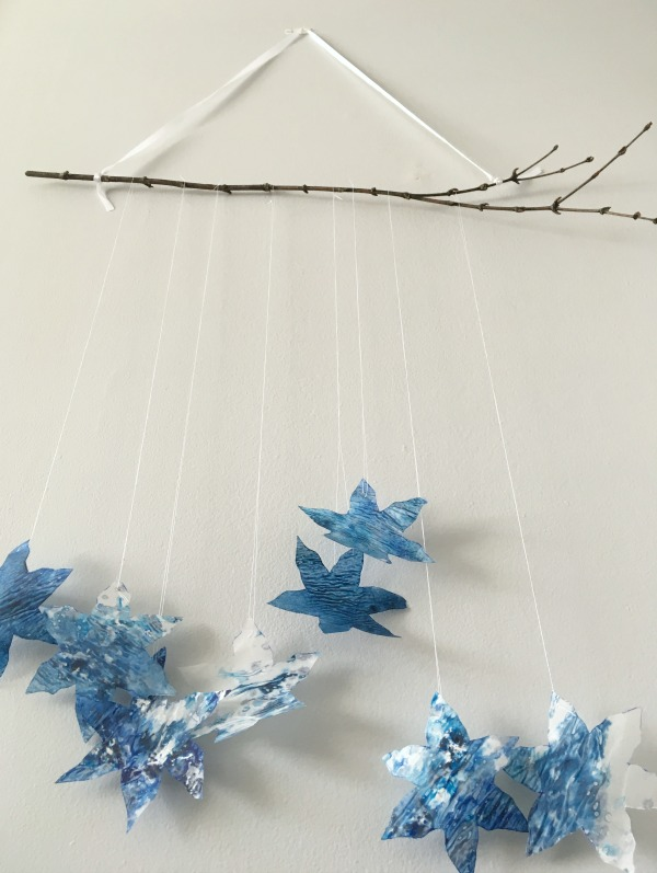 snowflake mobile on branch with ribbon