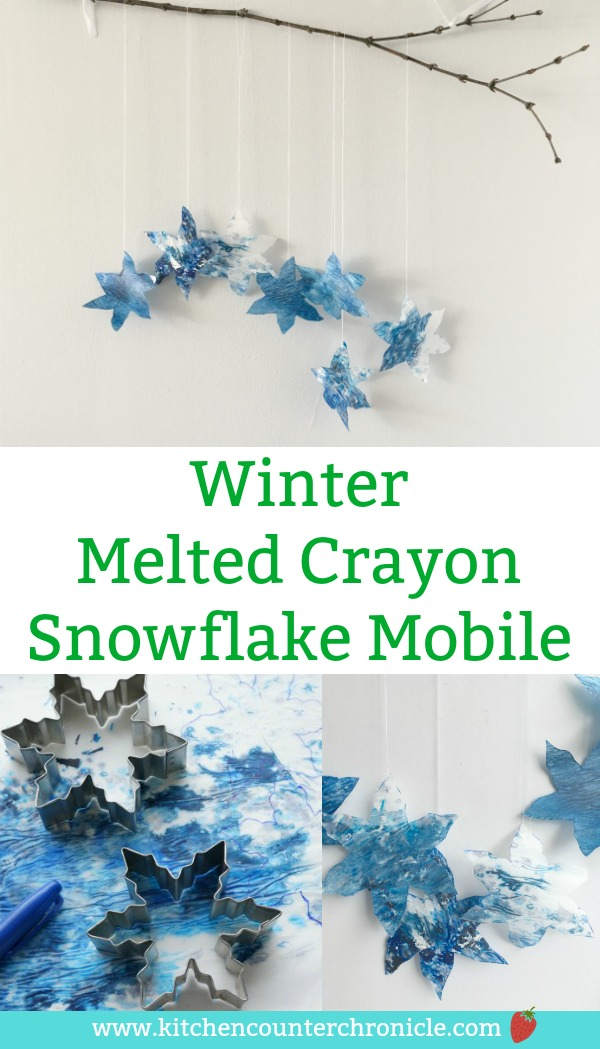 winter melted crayon snowflake mobile - A lovely winter craft for kids to make. Gather up your old crayons and snowflake cookie cutters to make a beautiful snowflake mobile. #wintercraft #snowflake #snowcraft #mobilecraft #craftforkids