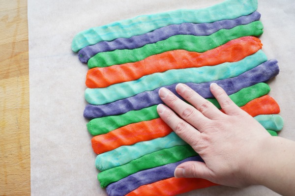 pressing rolls of coloured dough together
