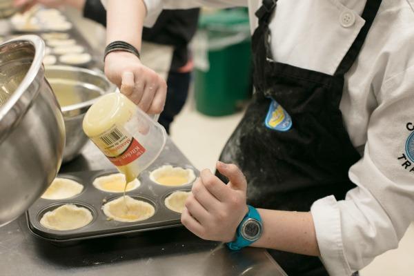 kid pouring butter tart filling