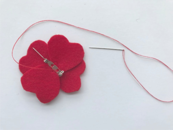 felt poppy with brooch pin being sewn on