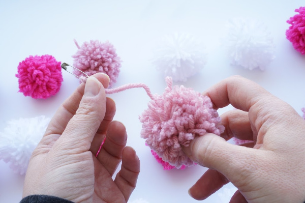feed the pom pom with safety pin onto yarn garland