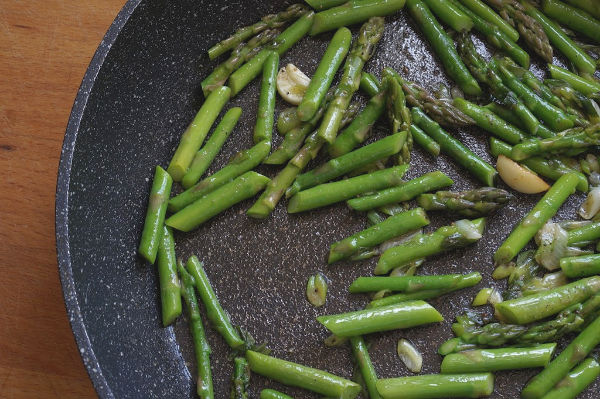 saute asparagus and onions in pan