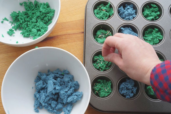 seeds being sprinkled into seed bomb muffin tin