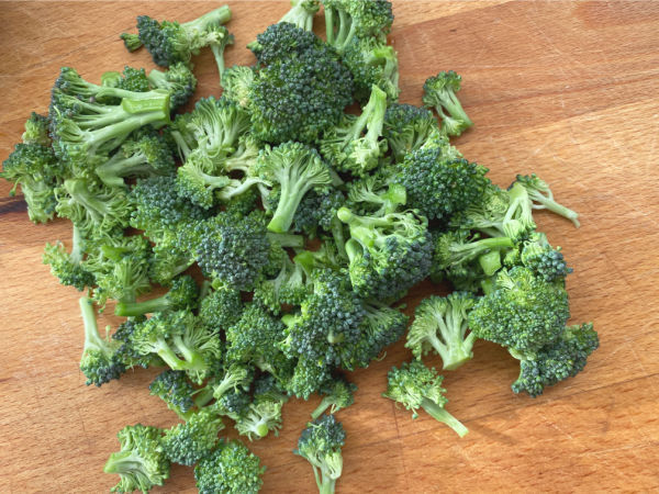 pile of broccoli florets on cutting board