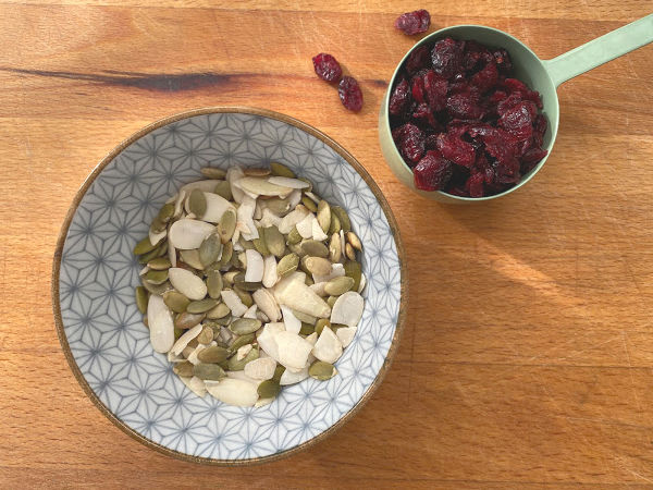 toasted slivered almonds, pumpkin seeds and cranberries on cutting board