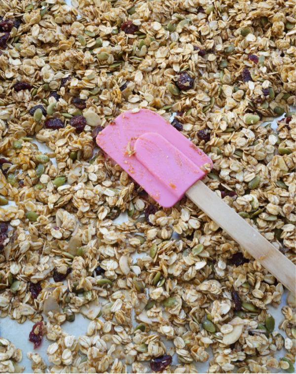 unbaked pumpkin spice granola spread on baking sheet