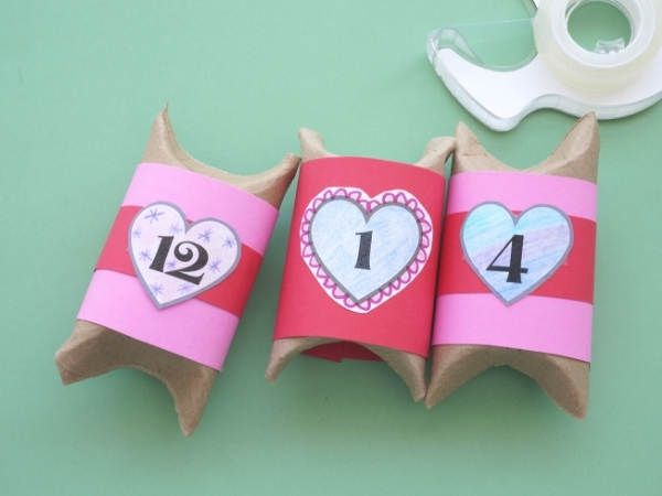 toilet paper roll boxes wrapped in pink paper and numbers taped on