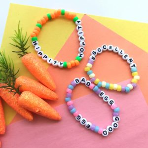 close up of easter bead friendship bracelet craft for tween on colourful backdrop with toy carrots