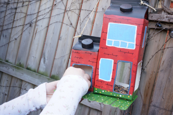 milk carton bird feeder being filled with seed and hanging from tree with child's hand