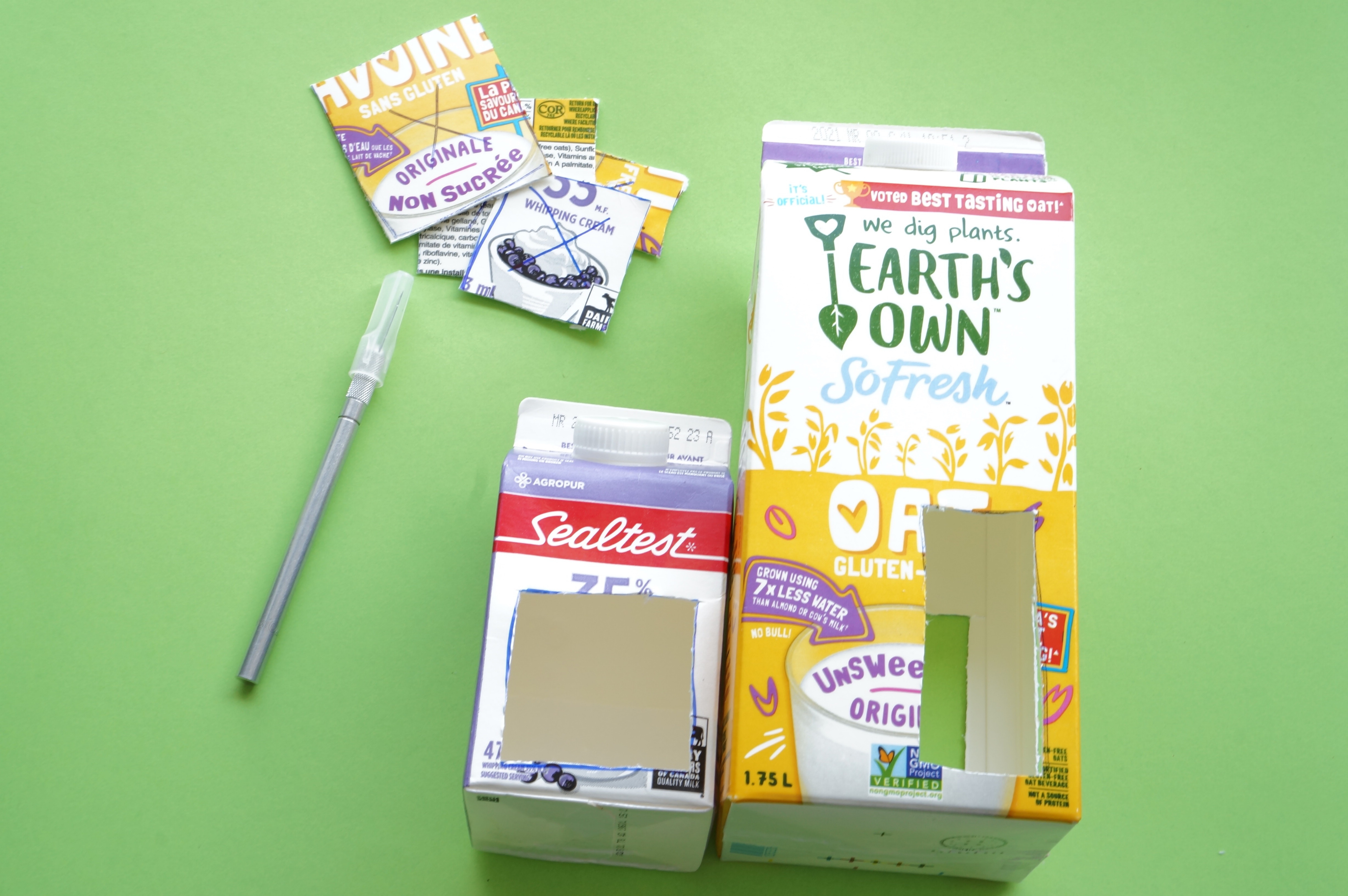 milk cartons with utility knife and openings cut out for bird feeder diy