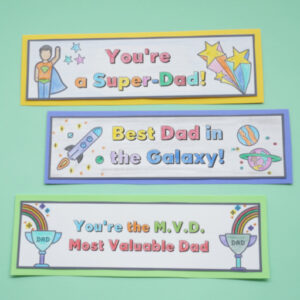 3 colouring fathers day bookmarks done on table
