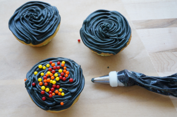 bbq grill cupcakes with black icing and red orange and yellow candy balls on top