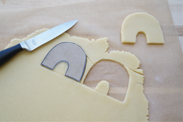 rainbow cardboard cookie cutter cut out of dough