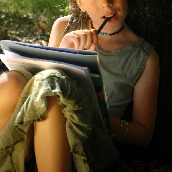 tween writing a story under a tree