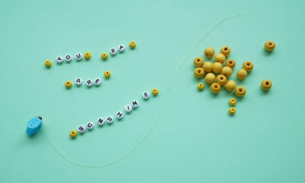 letter beads and yellow beads with stretchy thread